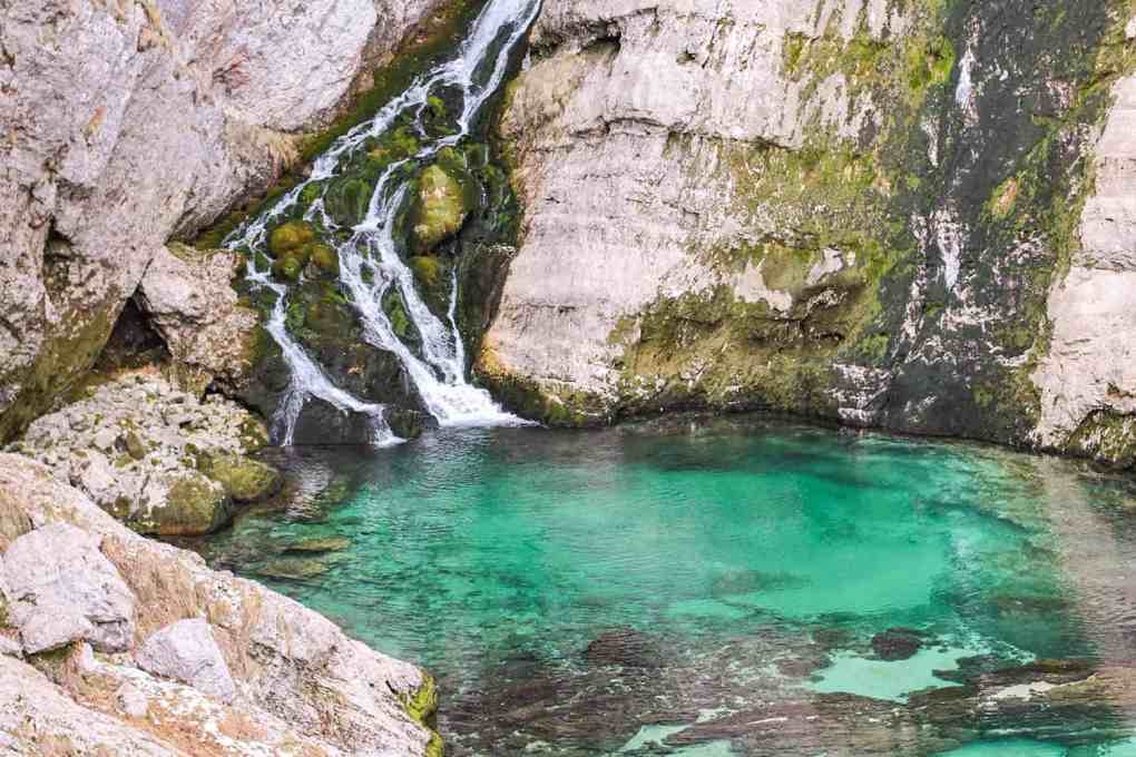 Waterfall coming down craggy rocks into an emerald green pool