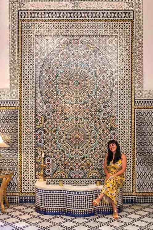 Woman sitting on the edge of a Moroccan mosaic fountain