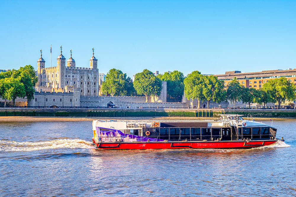 River Cruise boat on the river with the Tower of the London in the background