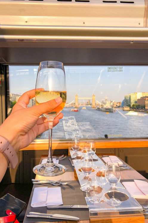 Holding a glass of prosecco with a table laid for dinner and a view of Tower Bridge in London in the background