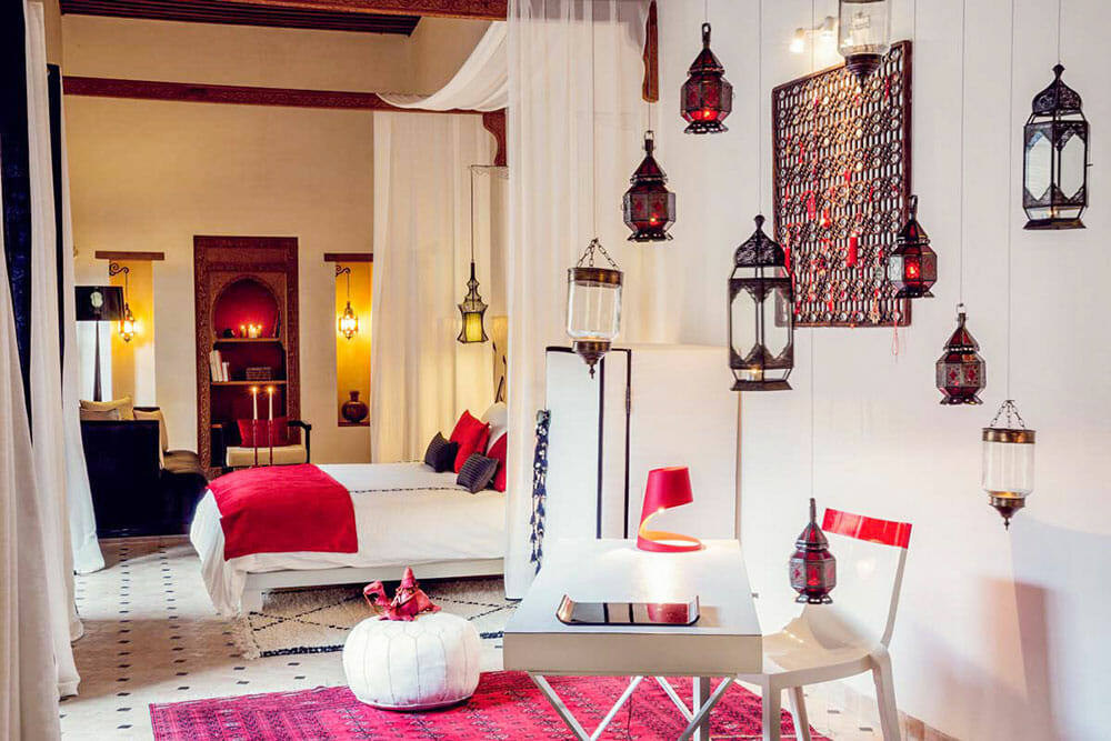 Room with bed decorated in white and red with Moroccan lanterns hanging from the wall
