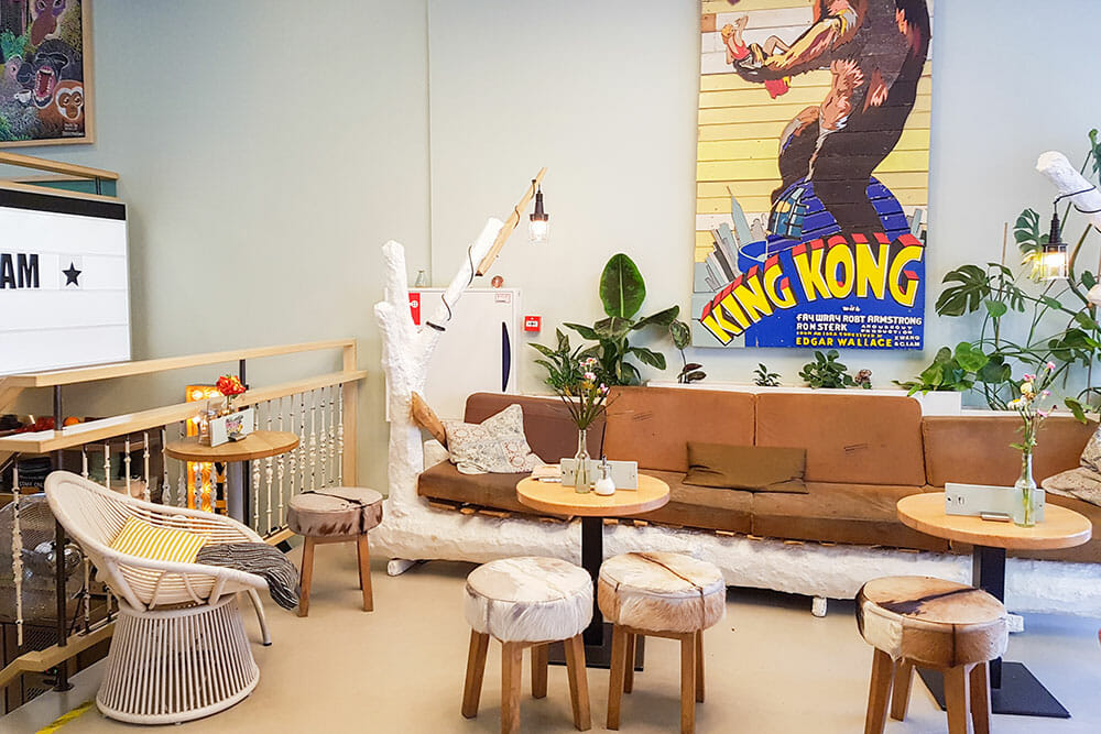 Social space with small tables and stools with a sofa and a poster reading King Kong. This is one of the best hostels in Rotterdam