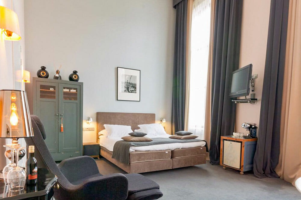 Room decorated in duck egg blue with a double bed and a double cabinet and floor to ceiling windows and curtains