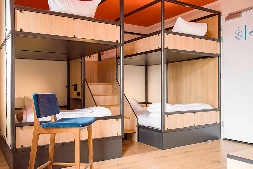 Room with four bunk beds with wooden steps to the top bunks and a blue chair