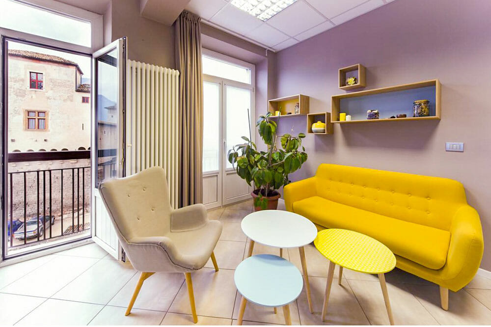 Sitting area with stylish yellow sofa, beige armchair and three small round tables