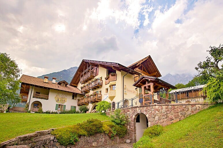 Alpine style three storey chalet with wooden balconies with a small bridges next to it