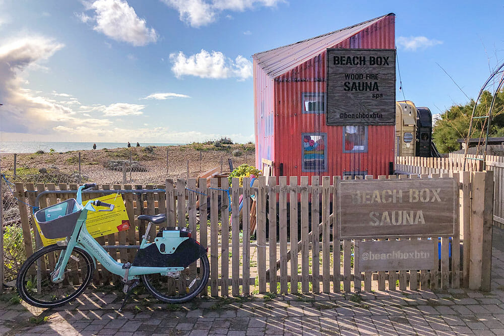 Bike parked outside a picket fence with a sign reading Beach Box Sauna and a red corrugated iron small building with the beach in the background
