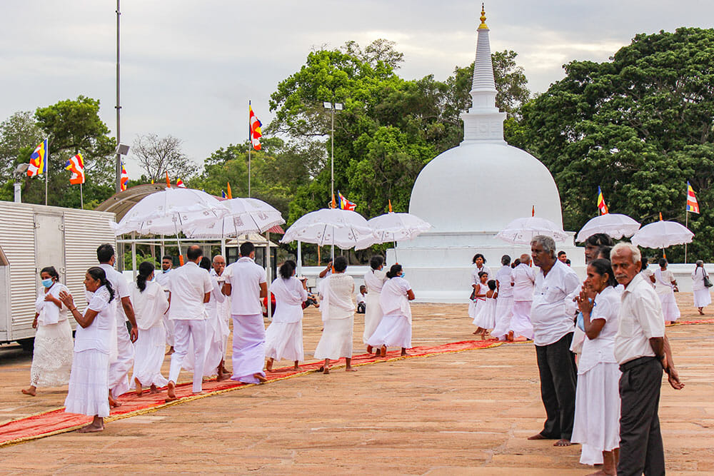 People dressed in white with white umbrellas walking towards a white pagoda