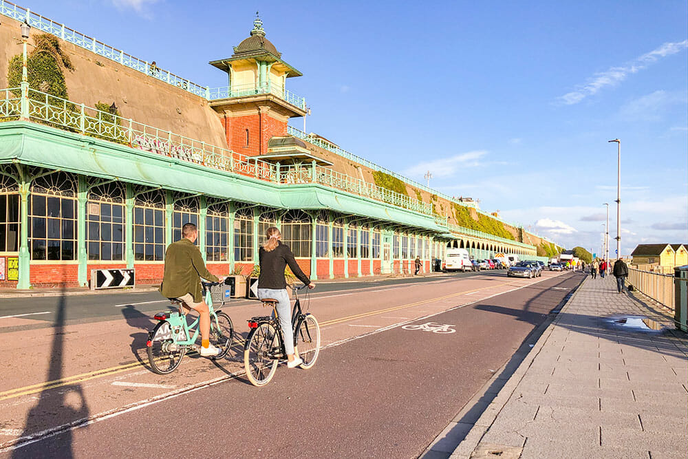 Two people cycling past green Victorian galleries in Brighton