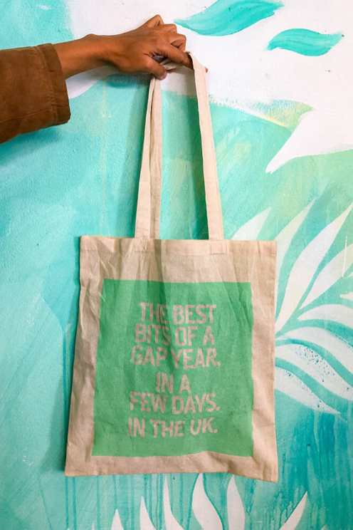 Hand holding a tote canvas bag reading 'the best bits fo a gap year, in a few days, in the uk'