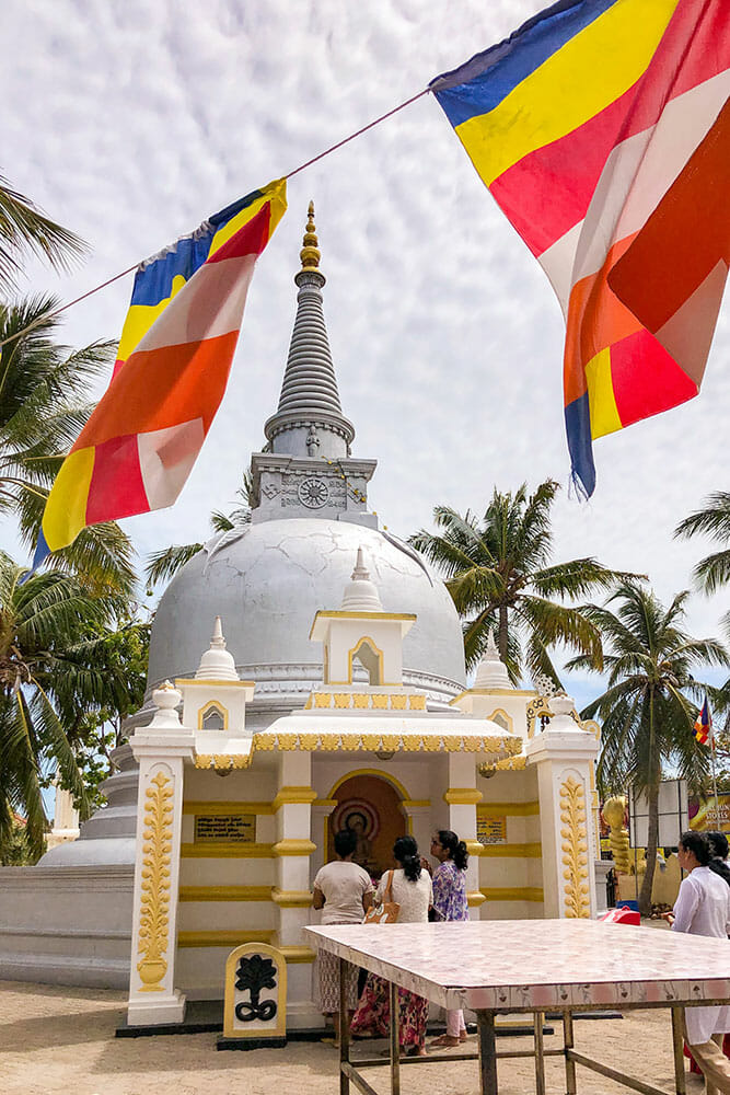 White pagoda with people praying next to it and buddhist flags hanging over it