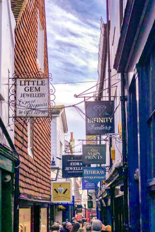 Narrow lane with traditional shop signs hanging down
