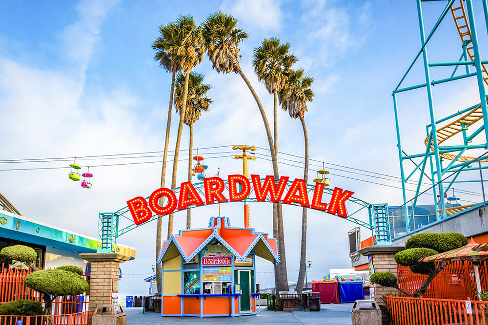 Entrance to the amusement park with an act with the words Boardwalk and palm trees behind it