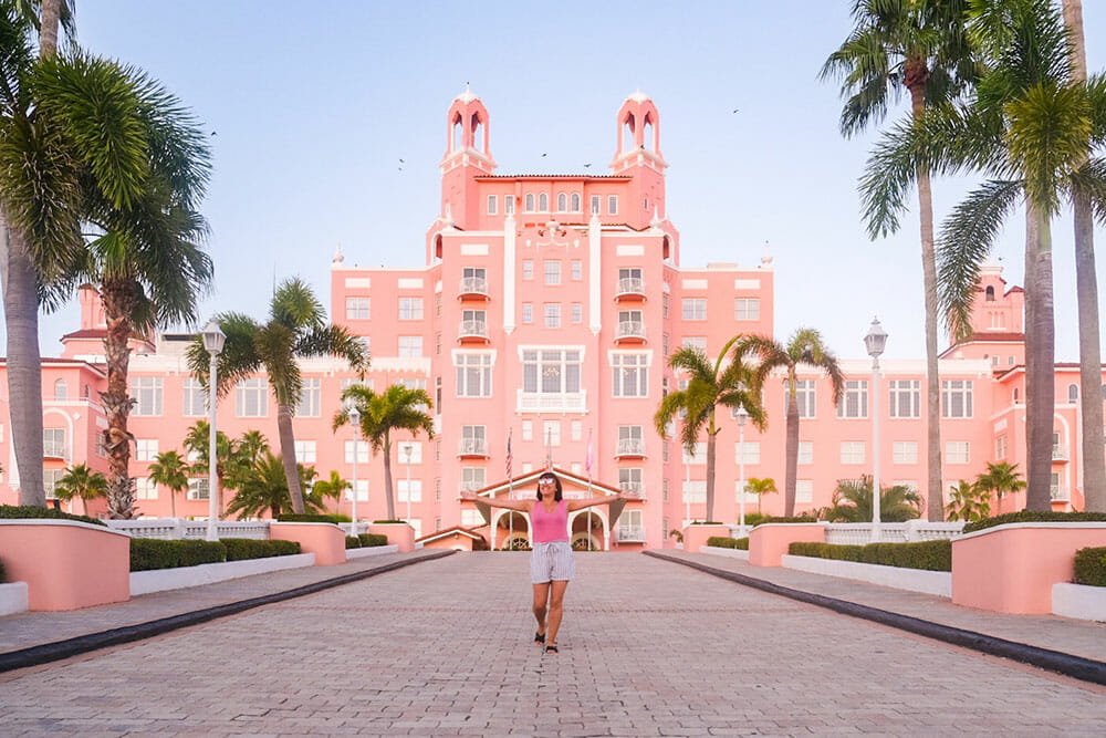 Woman standing with open arms in the middle of a paved road lined with palm trees and a seven storey pink building behind. The Don CeSar hotel is a must stop to anyone spending at least one day in St Pete