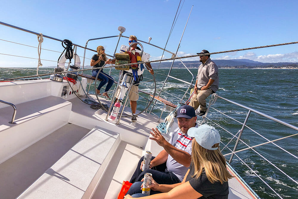 Five people on a racing yacht tilting as it goes at speed