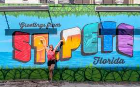 Woman standing in front of a colourful mural that reads Greetings from St Pete Florida