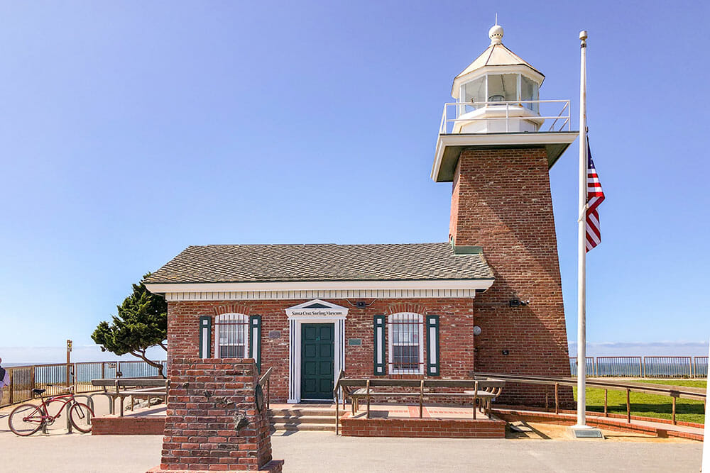 Small red brick lighthouse with the US flag outside
