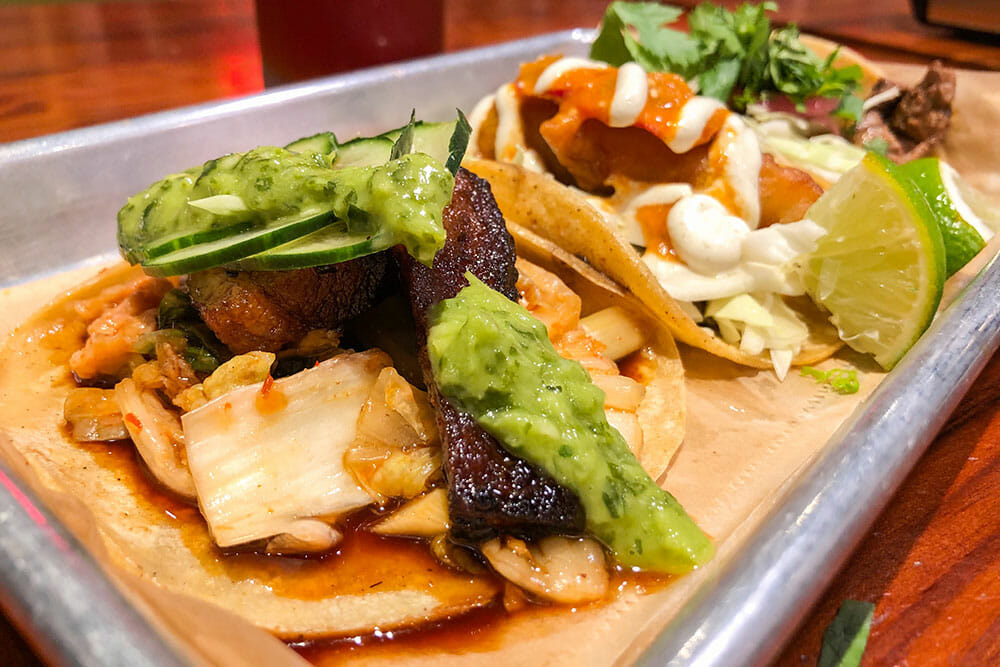A plate of tacos with pork belly, fish, lime and a green sauce