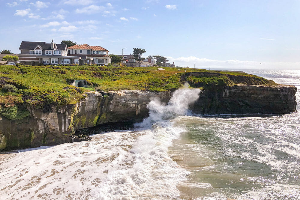 Waves crushing on to the cliffs with houses on top of the cliffs