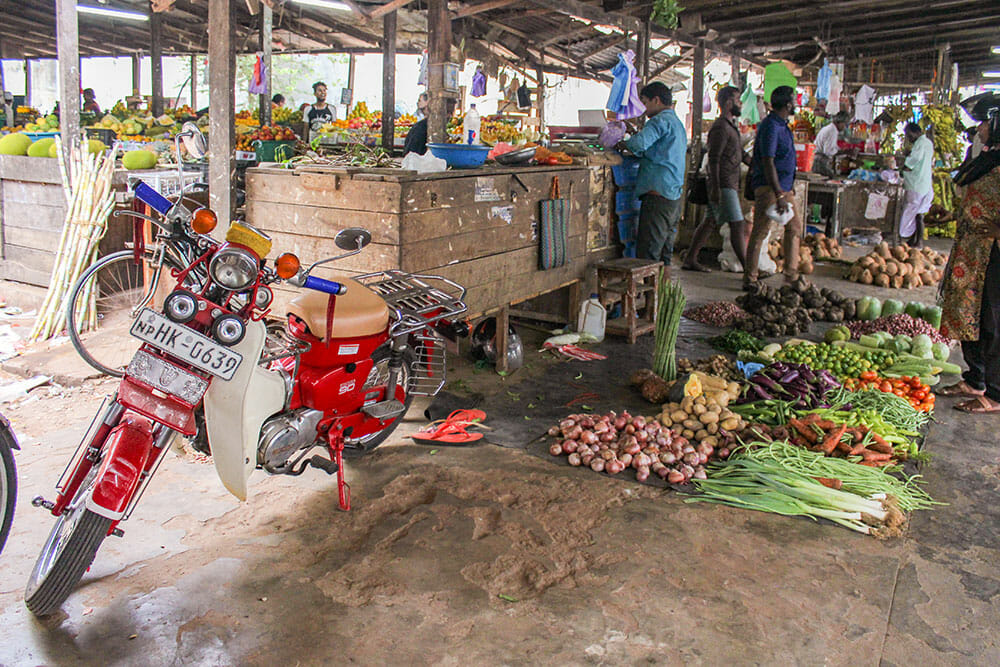 Fresh produce market with wooden stalls and vegetables laid on the floor, with men shopping around and a red motorbike parked next to the stalls