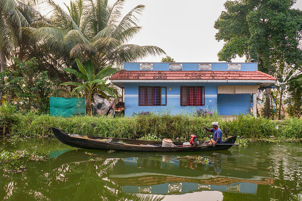 Man on a long narrow boat rowing past a small blue house in the Kerala Backwaters