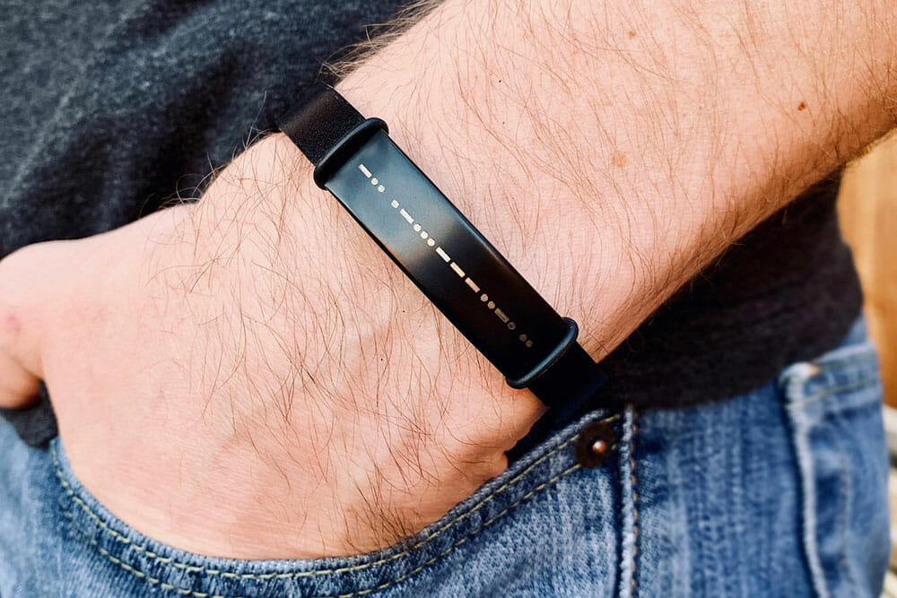 Man's wrist wearing a black bracelet with a message in morse code