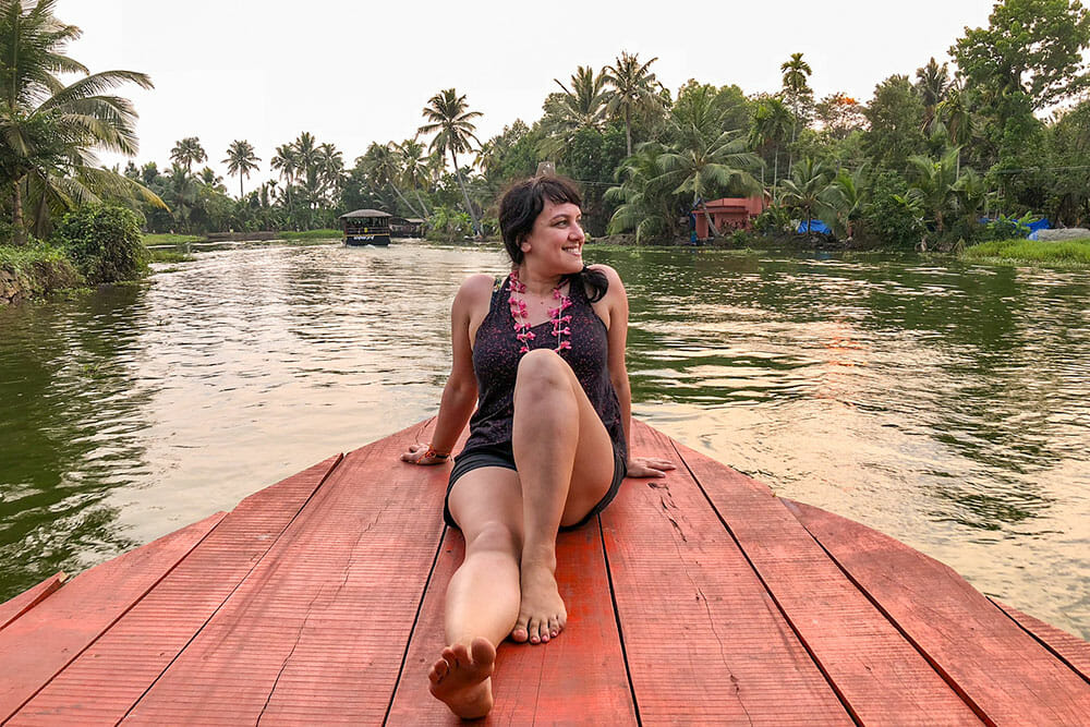 Woman sitting at the front of a boat while navigating the river like backwaters with palm trees all around