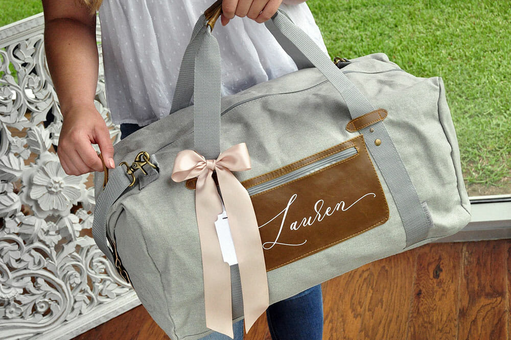 Woman holding a grey canvas duffel bag with the name Lauren on the pocket and with a pink ribbon