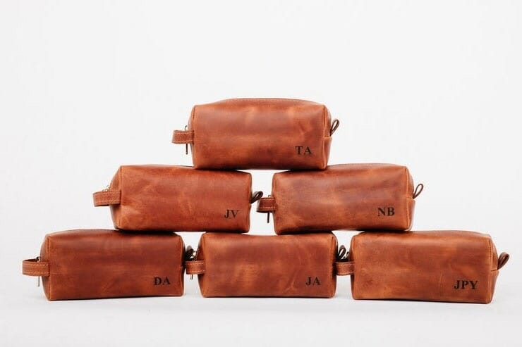 Six brown leather toiletry bags arranged on a pyramid with personalised initials