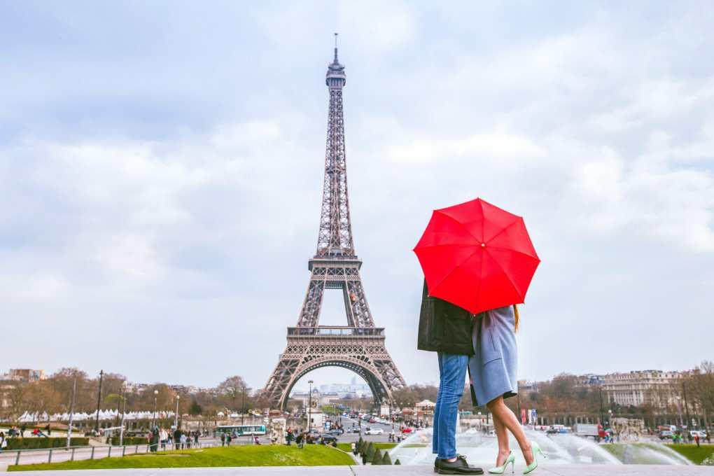 honeymoon in Paris, couple kissing behind red umbrella against Eiffel tower
