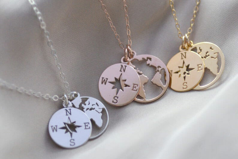 Three necklaces with compass and world map pendants in silver, rose gold and gold colours