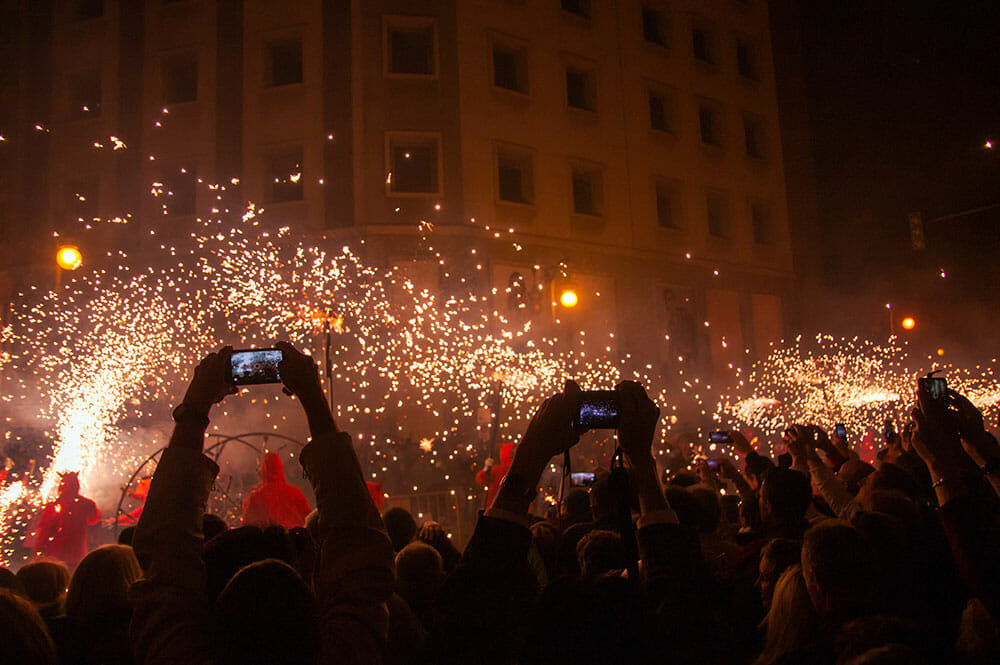 Crowds watching a fire parade and recording it on their phones