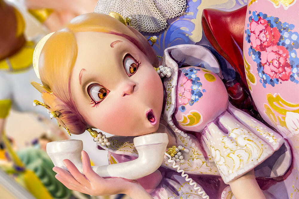 Falla sculpture depicting a cartoon-like fallera girl on the phone