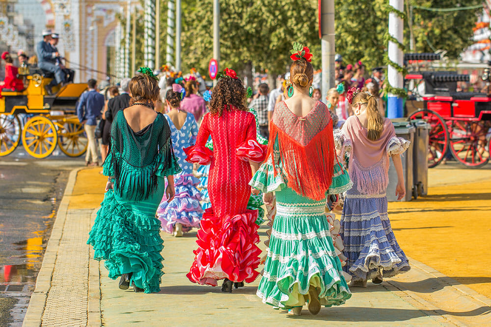 A group of women dressed in colourful flamenco outfits walking away towards the feria