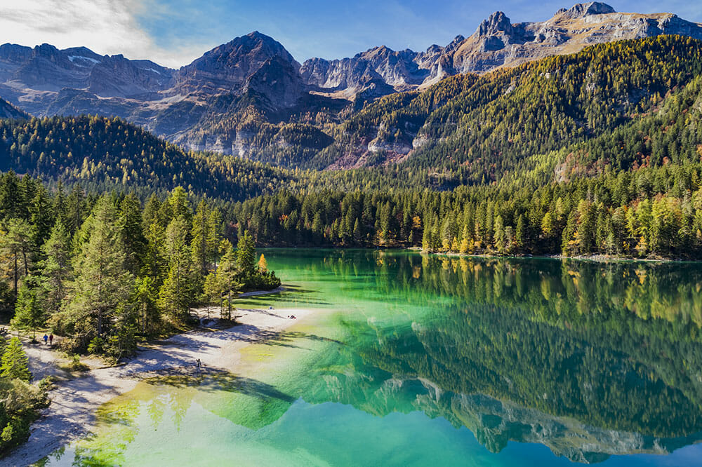 Emerald coloured lake with white beach surrounded by alpine forest and mountains. One of the best hikes in the Dolomites, Italy