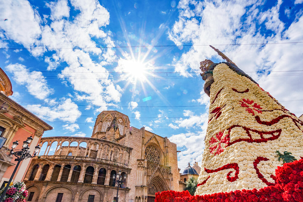 Giant virgin with a cape covered in flowers standing next to a gothic cathedral