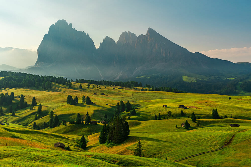 Green undulating green fields with dramatic mountains in the background