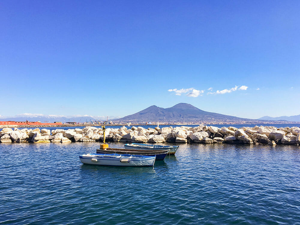Small rowing boats in the sea and Vesuvius volcano in the background