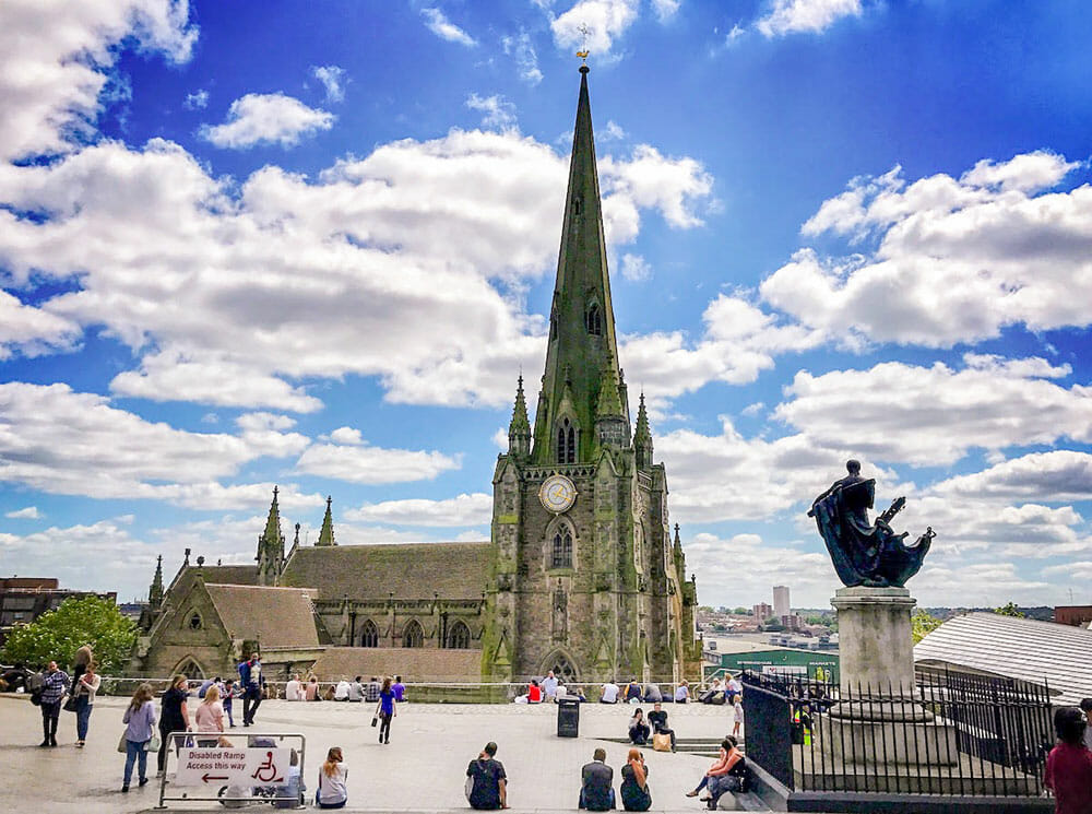 Square with people walking around and cathedral with tall spire in the background