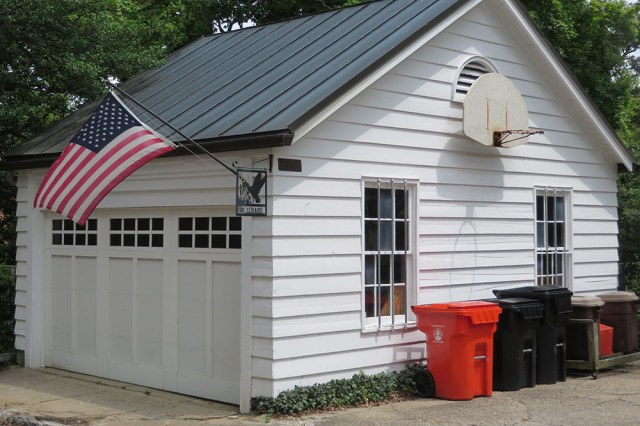 Horizontal lapped siding with mitered corners and carriage house doors distinguish this garage at 2425 Cherokee Parkway. (Christopher Quirk)