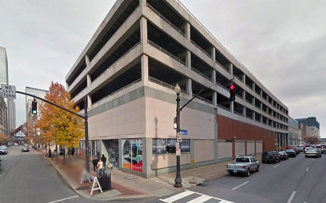 This parking garage will be renovated and existing retail restored. (Via Google)