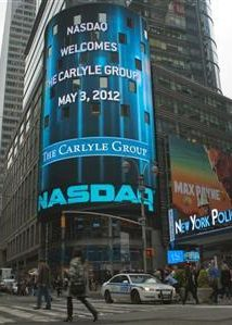 Passersby walk in front of video monitors announcing the Carlyle Group's listing on the NASDAQ market site in New York's Times Square