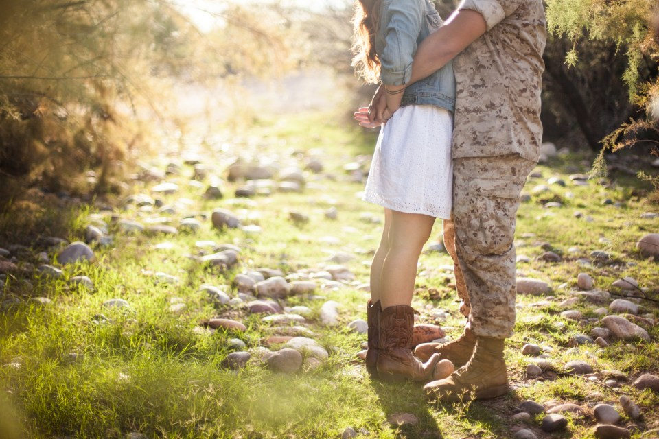 marine wrapping his arms around girl wearing cowgirl boots