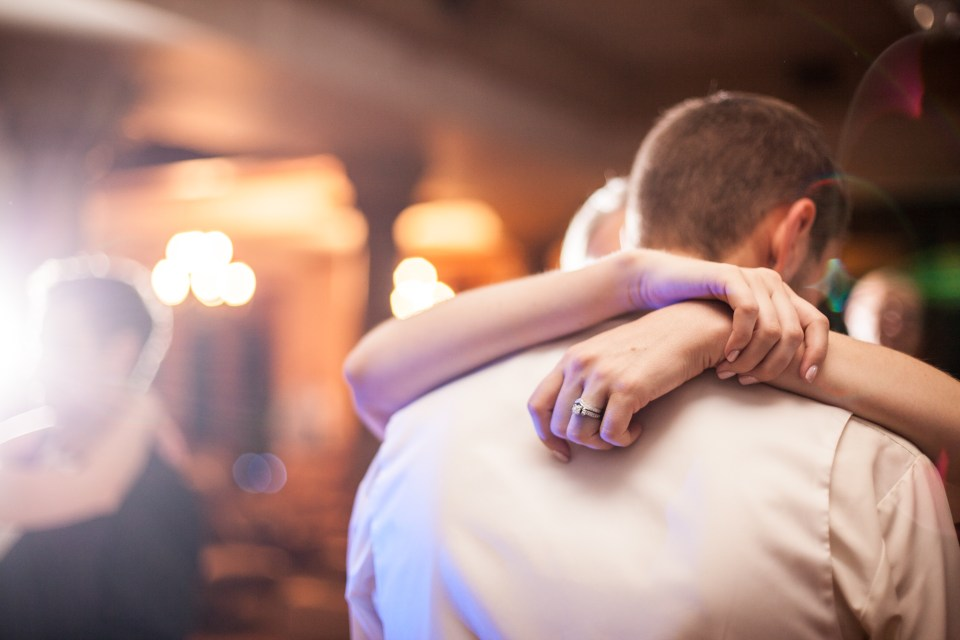 brides hands around grooms neck slow dancing