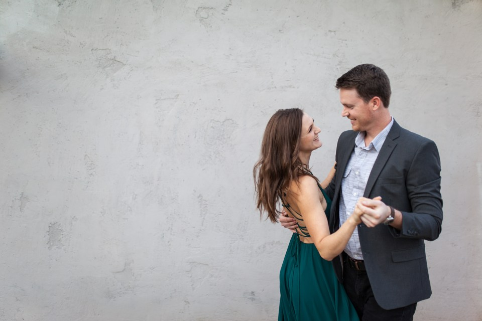 downtown phoenix engagement photos engagement pictures engagement photographer long flowy green dress from lulus for engagement session with gray background dancing couple engagement pictures inspiration