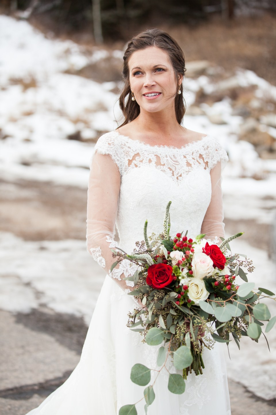 winter bride ideas with long sleeve lace sweetheart wedding dress and red rose bouquet in the snow