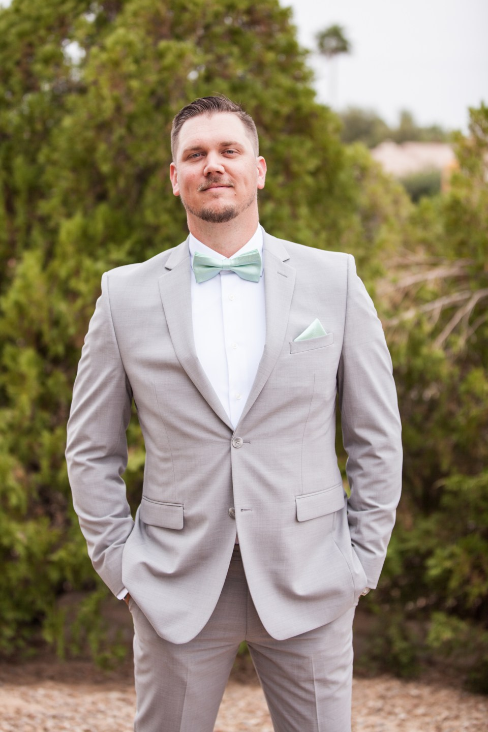 groom in gray suit with teal blue bow tie and pocket square