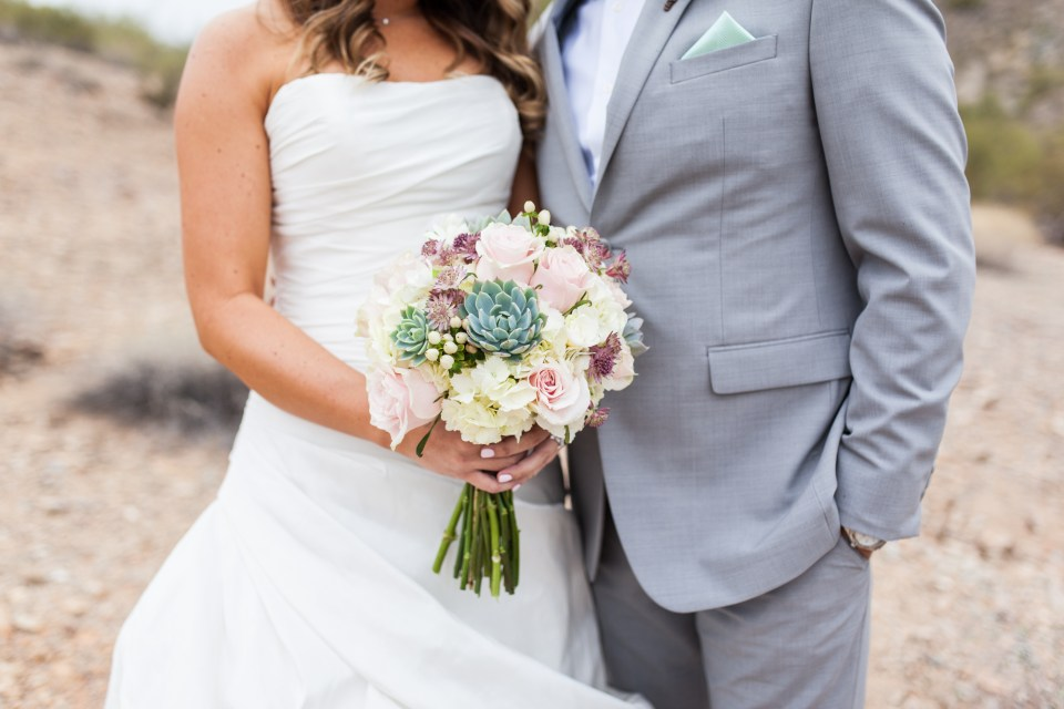 bride and groom with succulent wedding bouquet with pink roses