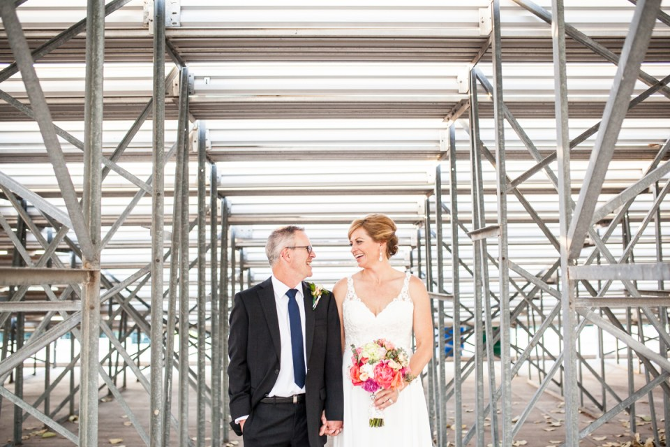 bride and groom behind the bleachers