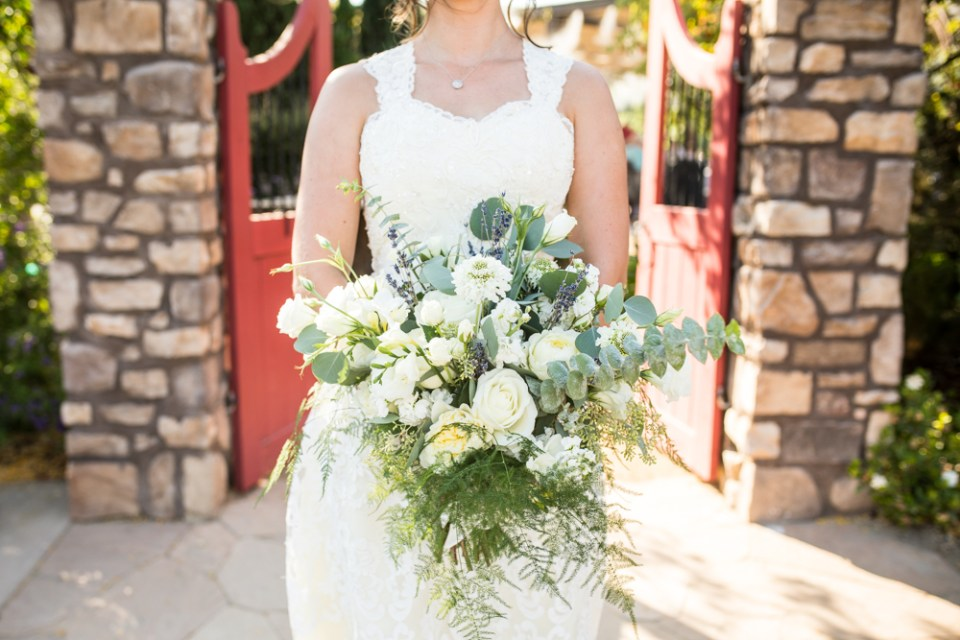 bride in lace wedding dress with large bridal bouquet with greenery and white flowers